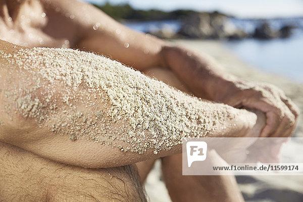Sandiger Unterarm eines Mannes  der sich am Strand entspannt  Nahaufnahme