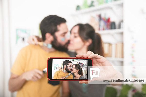 Junges Paar  das sich küsst und einen Selfie mit Pinseln nimmt.