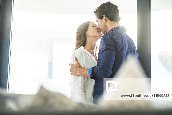 Junges verliebtes Paar küsst sich am Fenster