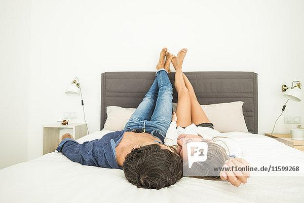 Verliebtes junges Paar im Bett liegend mit erhobenen Füßen