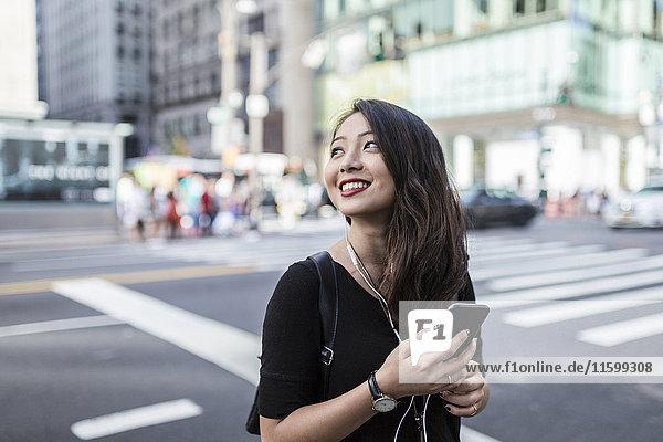 USA  New York City  Manhattan  junge Frau beim Musikhören mit Handy und Kopfhörer auf der Straße