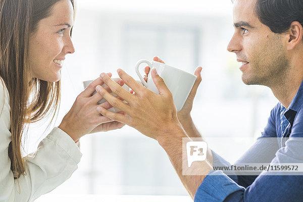 Junges verliebtes Paar mit Kaffeetassen
