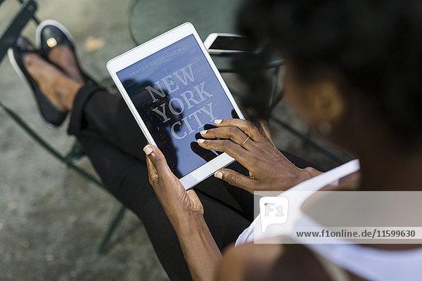 USA  New York City  Frau im Park sitzend mit Reiseführer auf Tablett