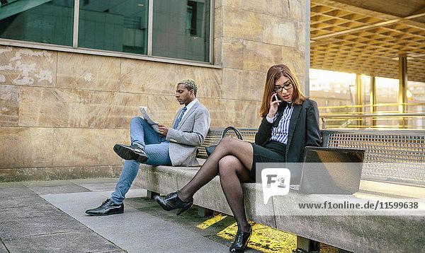 Junger Geschäftsmann und Frau sitzen auf der Bank  Frau spricht am Telefon