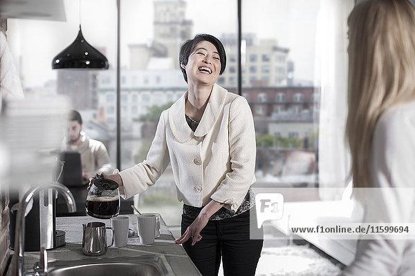 riends lachend in offener Küche mit Blick auf die Stadt