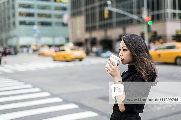 USA  New York City  Manhattan  junge Frau  die Kaffee trinkt  um auf die Straße zu gehen.