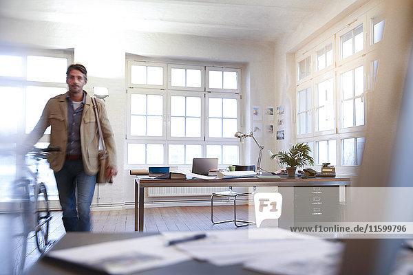 Mann mit Fahrrad in einem modernen informellen Büro
