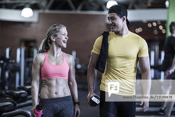 Fröhlicher junger Mann und Frau im Fitnessstudio