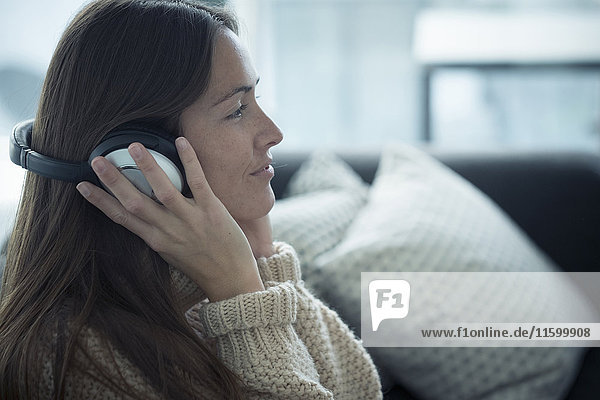 Smiling young woman listening to music at home