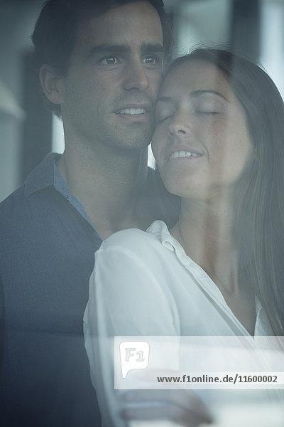 Verliebtes junges Paar hinter der Fensterscheibe