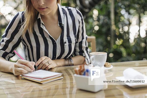Geschäftsfrau sitzt auf dem Bürgersteig Cafe Schreiben in Notebook