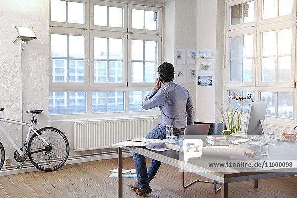 Mann mit Handy in einem modernen informellen Büro
