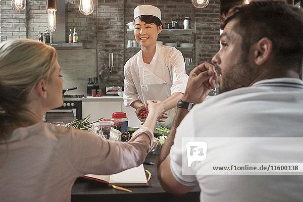 Köchin mit Studenten im Kochkurs