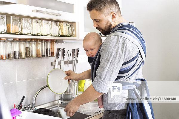 Vater mit Babysohn im Tragetuch zu Hause beim Abwaschen