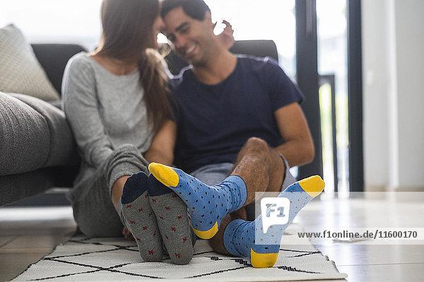 Junges Paar in gemusterten Socken entspannt zu Hause