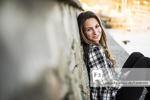 Frau im Freien sitzend  an der Wand lehnend