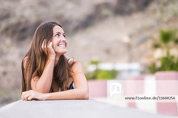 Porträt einer lächelnden Frau mit Anlehnung an eine Wand