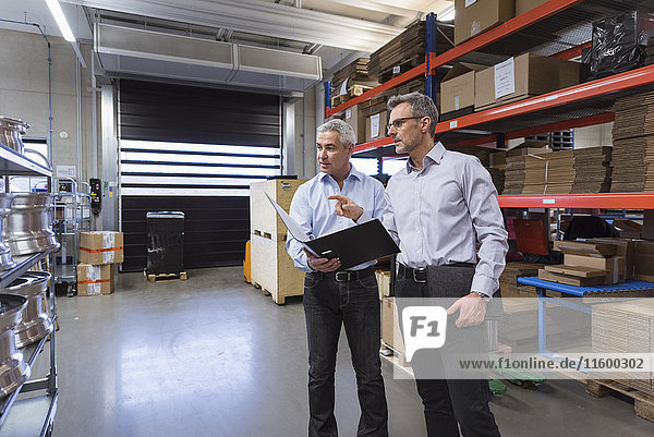 Zwei Geschäftsleute in der Fabrikhalle,  die sich unterhalten