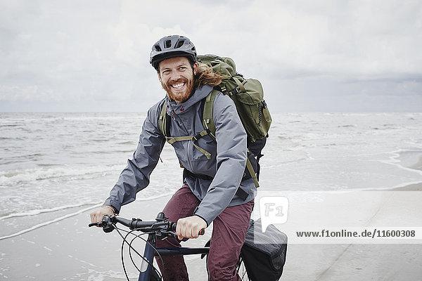 Deutschland  Schleswig-Holstein  St. Peter-Ording  glücklicher junger Mann auf dem Fahrrad am Strand