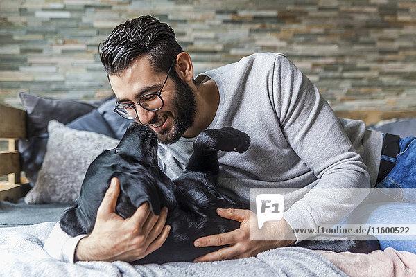 Lächelnder Mann  der mit seinem Hund auf der Couch zu Hause kuschelt.