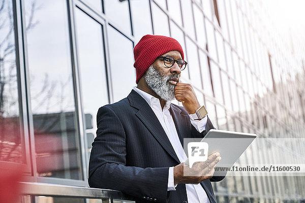 Älterer Geschäftsmann mit digitalem Tablett auf der Straße