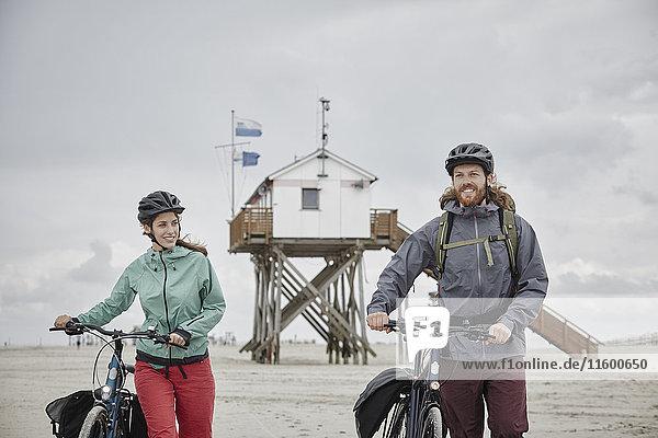 Deutschland  Schleswig-Holstein  St. Peter-Ording  Paar beim Fahrradfahren am Strand