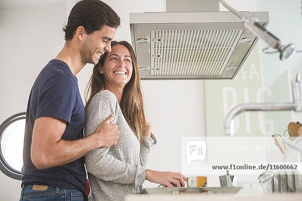 Ein glückliches junges Paar  das in Kaffeetassen in der Küche verliebt ist.
