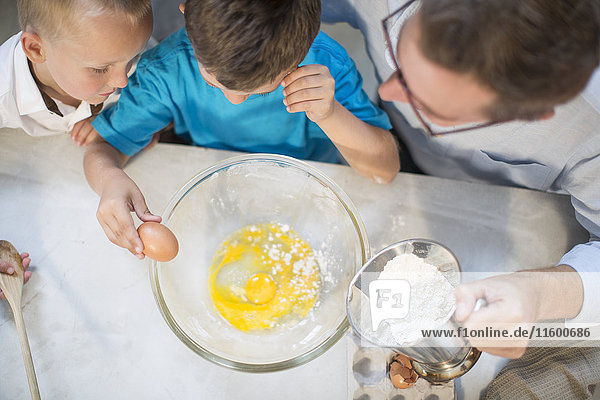 Father and two boys baking in kitchen