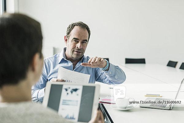 Geschäftsmann und Geschäftsfrau diskutieren im Konferenzraum