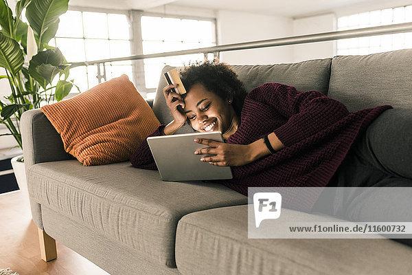 Lächelnde junge Frau auf der Couch liegend mit Kreditkarte und Tablette