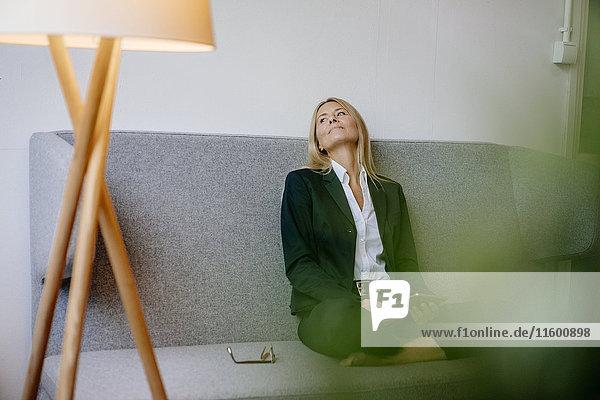 Entspannte Geschäftsfrau auf der Couch sitzend mit Tablette