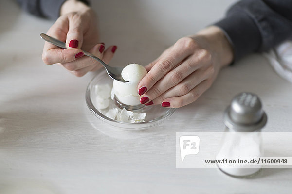 Close-up of woman eating boiled egg