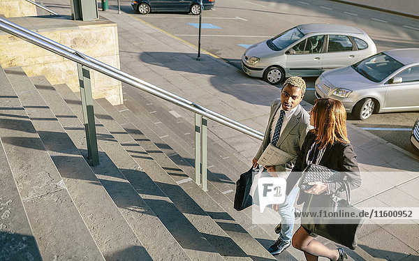 Junger Geschäftsmann und Frau beim Treppensteigen