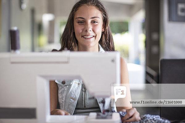 Porträt des lächelnden Mädchens an der Nähmaschine Porträt des lächelnden Mädchens an der Nähmaschine