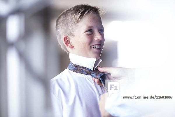 Vater hilft dem Sohn beim Binden seiner Krawatte