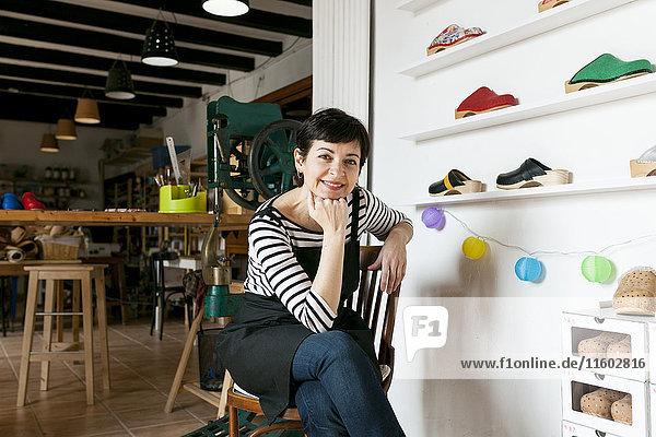 Porträt der selbstbewussten Holzschuhmacherin in ihrer Werkstatt Porträt der selbstbewussten Holzschuhmacherin in ihrer Werkstatt