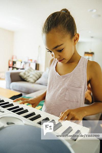 Mixed Race girl playing music on keyboard