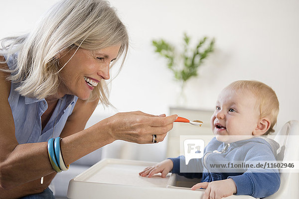 Smiling Caucasian grandmother feeding baby grandson in high chair