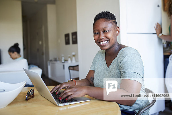 Smiling Black woman using laptop at table