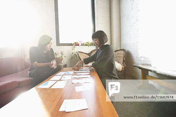 Women examining paperwork on coffee table
