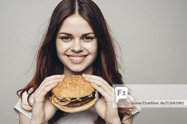 Smiling Caucasian woman holding cheeseburger