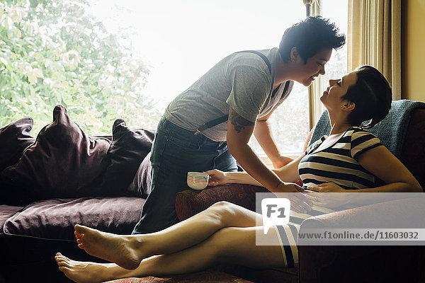 Pregnant lesbian couple kissing in livingroom