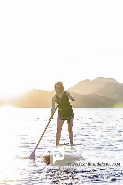 Caucasian woman on paddleboard in river