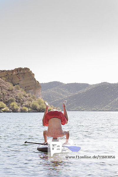 Hispanic man doing headstand on paddleboard in river