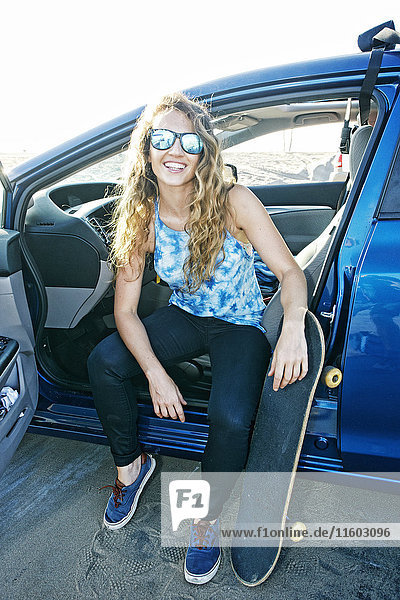 Caucasian woman sitting in car with skateboard