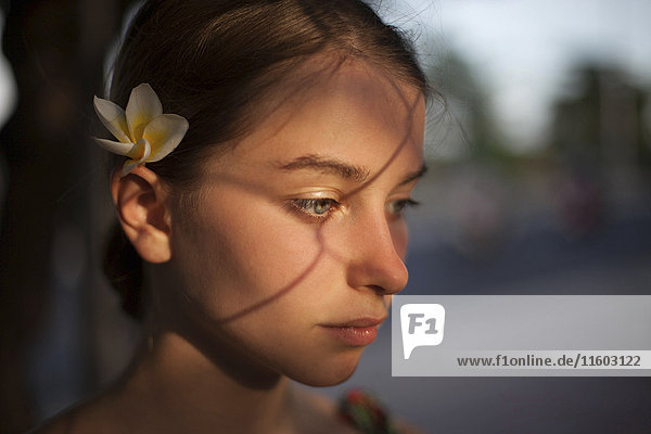 Pensive Caucasian woman with flower in hair