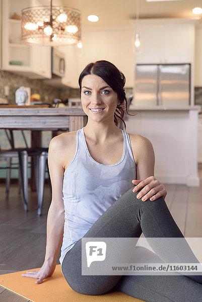 Smiling Caucasian woman sitting on exercise mat