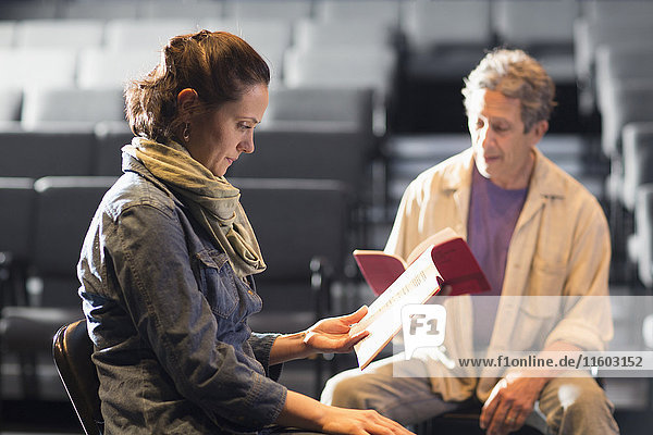 Caucasian actors rehearsing with scripts in theater