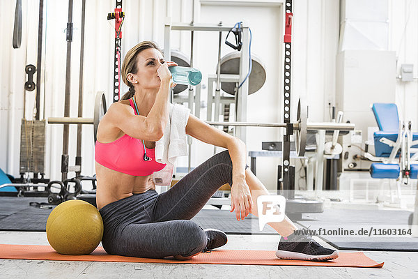Woman sitting with heavy ball drinking water in gymnasium