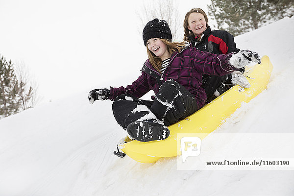 Smiling girls sliding in toboggan on hill in winter